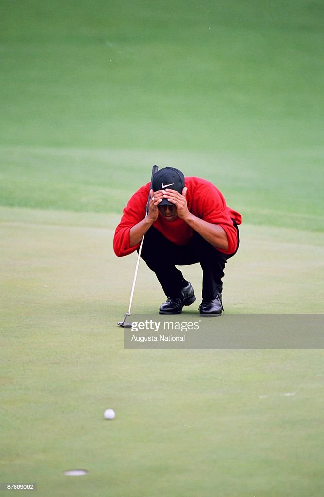 Tiger Woods lines up his putt on the 18th hole during the 1997 Masters Tournament at Augusta National Golf Club on April 13, 1997 in Augusta, Georgia.