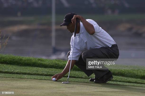 Tiger Woods lines up his putt on the sixth hole 16 June 2000 at the second round of the US Open in Pebble Beach CA Woods is the current leader of the...