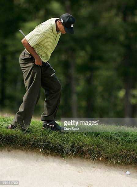 Tiger Woods locates his ball in the bunker at the fourth hole during the first round of the Deutsche Bank Championship at TPC Boston on August 31,...