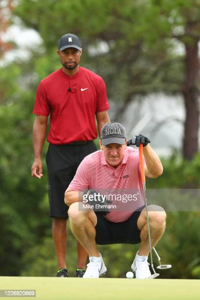 Tiger Woods looks on as former NFL player Peyton Manning lines up a putt on the fourth green during The Match Champions For Charity at Medalist Golf...
