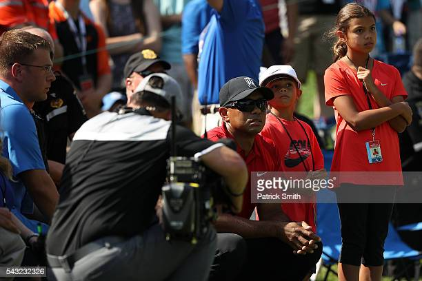 Tiger Woods looks on with his children Sam and Charlie during the final round of the Quicken Loans National at Congressional Country Club on June 26...