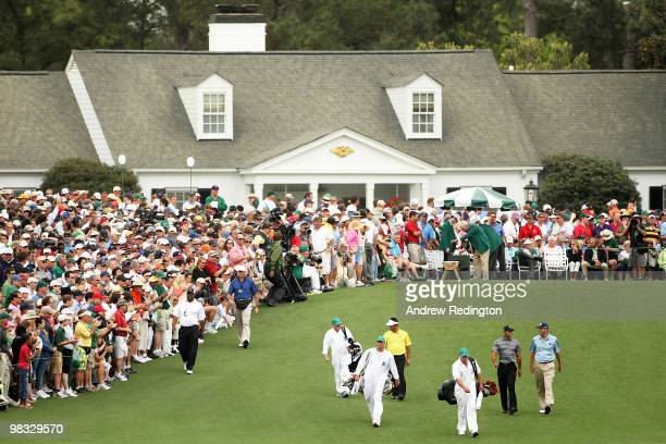 Tiger Woods, Matt Kuchar and K.J. Choi of Korea walk off the first tee with their caddies during the first round of the 2010 Masters Tournament at...