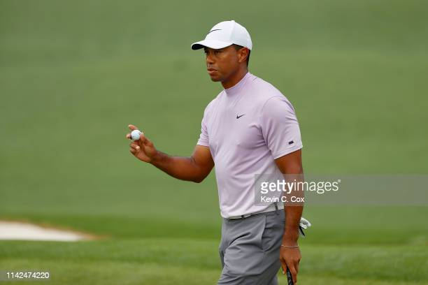 Tiger Woods of the United States acknowledges patrons after putting on the second green during the third round of the Masters at Augusta National...