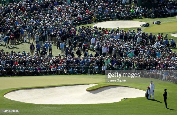 Tiger Woods of the United States and caddie Joe LaCava prepares to play on the second hole during the first round of the 2018 Masters Tournament at...