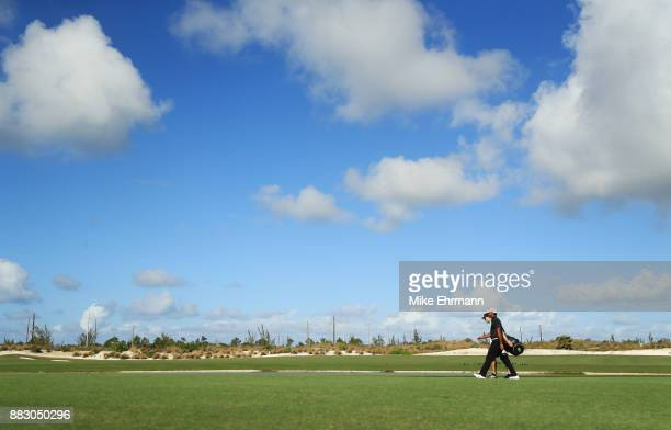 Tiger Woods of the United States and caddie Joe LaCava walk on the ninth hole during the first round of the Hero World Challenge at Albany Bahamas on...