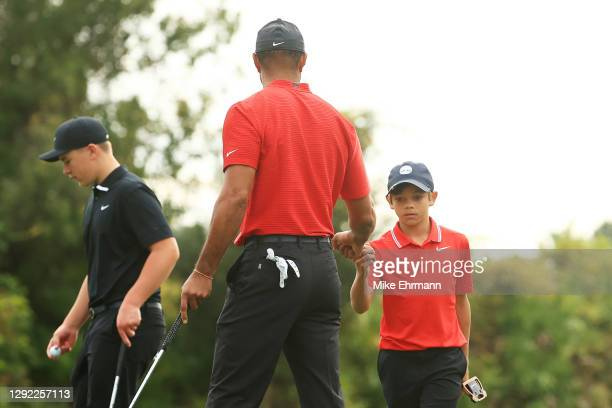 Tiger Woods of the United States and Charlie Woods fist bump on the third green during the final round of the PNC Championship at the Ritz-Carlton...