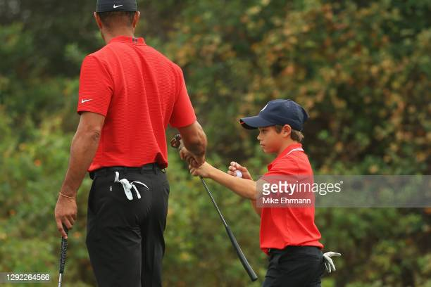 Tiger Woods of the United States and Charlie Woods fist bump on the seventh green during the final round of the PNC Championship at the Ritz-Carlton...