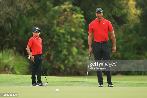 Tiger Woods of the United States and Charlie Woods line up a putt on the third green during the final round of the PNC Championship at the...