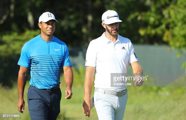 Tiger Woods of the United States and Dustin Johnson of the United States walk on the second hole during a practice round prior to the 2018 US Open at...
