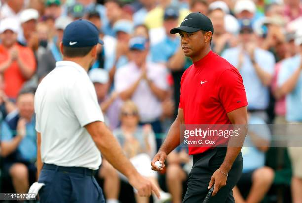 Tiger Woods of the United States and Francesco Molinari of Italy walk across the ninth green during the final round of the Masters at Augusta...