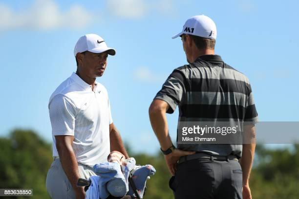 Tiger Woods of the United States and Justin Rose of England talk on the range prior to the second round of the Hero World Challenge at Albany Bahamas...