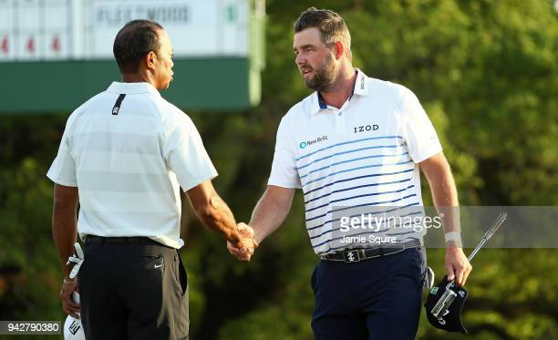 Tiger Woods of the United States and Marc Leishman of Australia shake hands on the 18th green during the second round of the 2018 Masters Tournament...