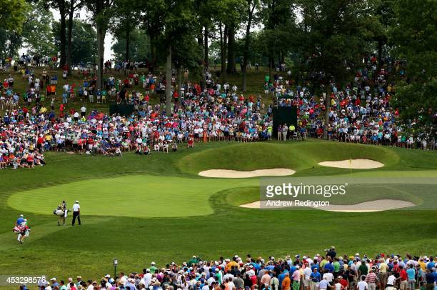 Tiger Woods of the United States and Padraig Harrington of Ireland walk onto the 14th green with their caddies during the first round of the 96th PGA...