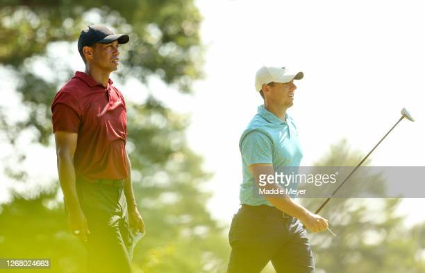 Tiger Woods of the United States and Rory McIlroy of Northern Ireland walk off the 12th tee during the final round of The Northern Trust at TPC...