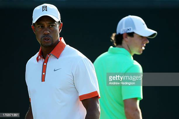Tiger Woods of the United States and Rory McIlroy of Northern Ireland walk across a green during a practice round prior to the start of the 113th...