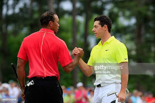 Tiger Woods of the United States and Rory McIlroy of Northern Ireland shake hands on the 18th green during the final round of the 2015 Masters...
