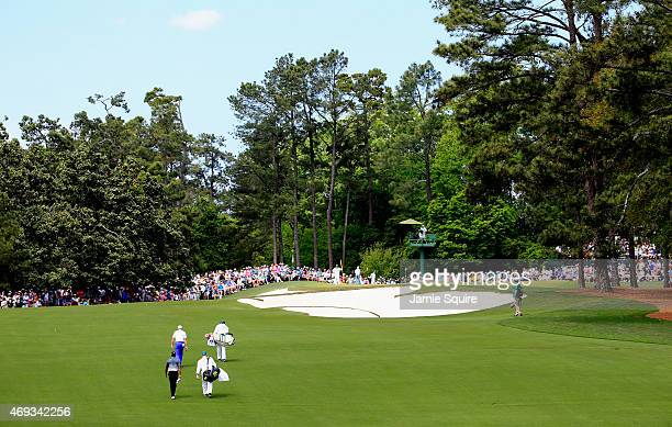 Tiger Woods of the United States and Sergio Garcia of Spain walk together with their caddies on the third hole during the third round of the 2015...