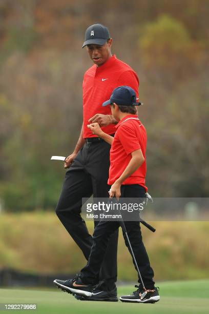 Tiger Woods of the United States and son Charlie Woods fist bump on the 15th green during the final round of the PNC Championship at the Ritz-Carlton...