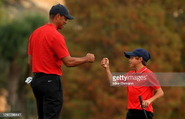 Tiger Woods of the United States and son Charlie Woods fist bump on the 18th hole during the final round of the PNC Championship at the Ritz Carlton...