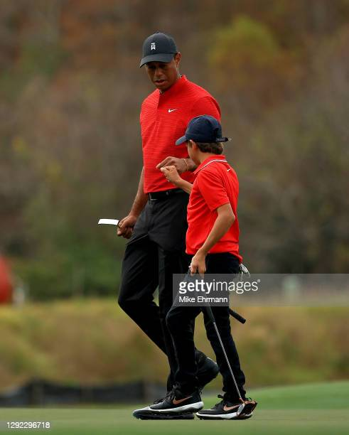Tiger Woods of the United States and son Charlie Woods fist bump on the 15th hole during the final round of the PNC Championship at the Ritz Carlton...