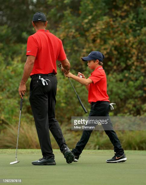 Tiger Woods of the United States and son Charlie Woods fist bump on the ninth hole during the final round of the PNC Championship at the Ritz Carlton...