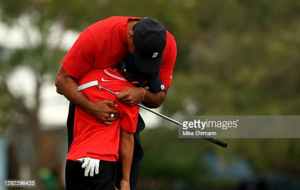 Tiger Woods of the United States and son Charlie Woods hug on the 18th hole during the final round of the PNC Championship at the Ritz Carlton Golf...