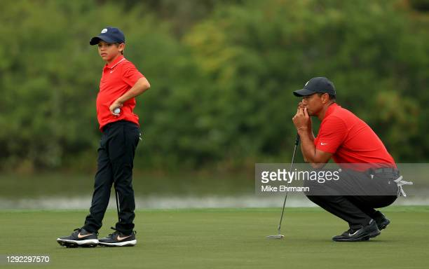 Tiger Woods of the United States and son Charlie Woods line up a putt on the 15th hole during the final round of the PNC Championship at the Ritz...