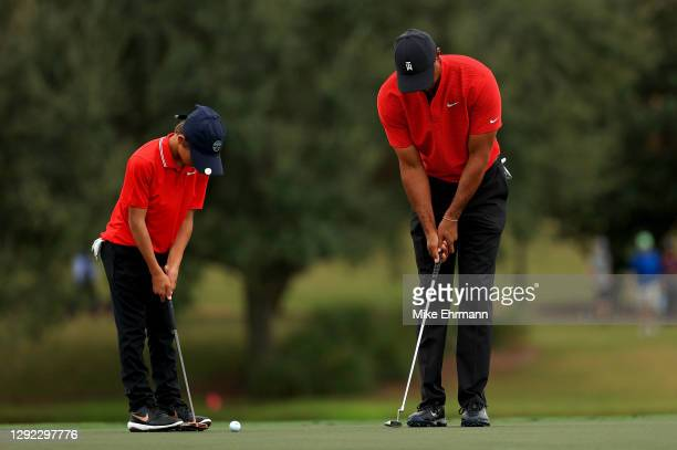 Tiger Woods of the United States and son Charlie Woods practice putting on the 14th hole during the final round of the PNC Championship at the Ritz...