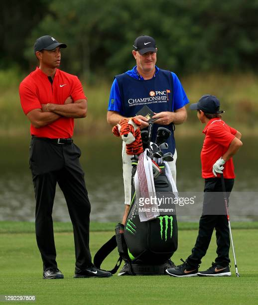 Tiger Woods of the United States and son Charlie Woods wait to hits their approach shot with caddie Joe LaCava during the final round of the PNC...