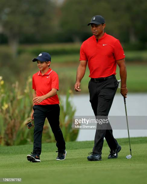 Tiger Woods of the United States and son Charlie Woods walk up the 14th hole during the final round of the PNC Championship at the Ritz Carlton Golf...