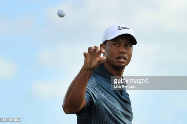Tiger Woods of the United States catches a ball as he warms up on the range prior to the third round of the Hero World Challenge at Albany Bahamas on...