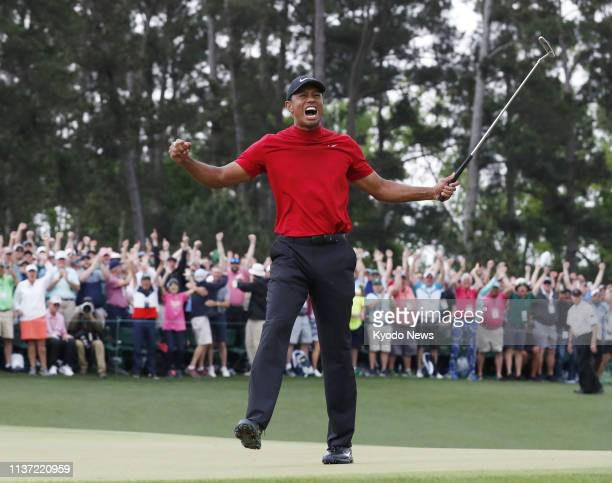Tiger Woods of the United States celebrates after sinking his putt on the 18th hole during the final round of the Masters Tournament in Augusta...