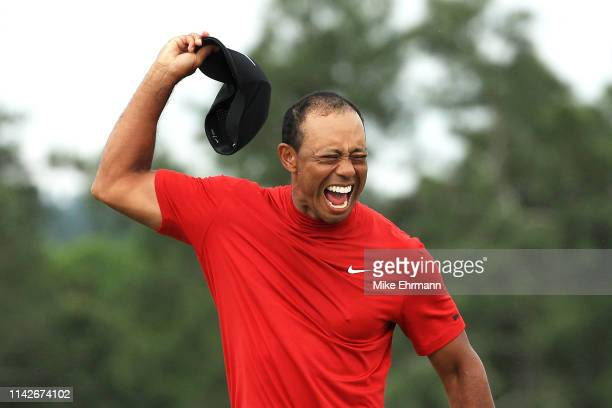 Tiger Woods of the United States celebrates after sinking his putt on the 18th green to win during the final round of the Masters at Augusta National...