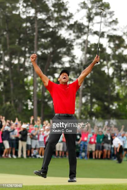 Tiger Woods of the United States celebrates after sinking his putt to win on the 18th green during the final round of the Masters at Augusta National...