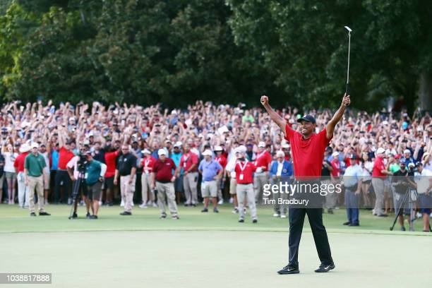 Tiger Woods celebrates his two stroke victory on the 18th hole green as fans watch behind him during the final round of the TOUR Championship the...