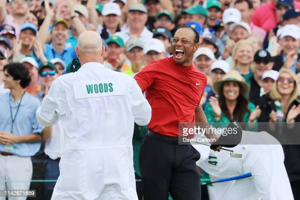 Tiger Woods of the United States celebrates with caddie Joe LaCava on the 18th green after winning during the final round of the Masters at Augusta...