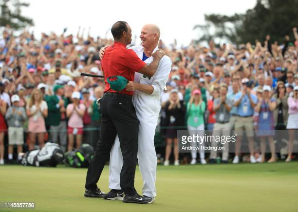Tiger Woods of the United States celebrates with caddie Joe LaCava on the 18th green after winning the Masters at Augusta National Golf Club on April...