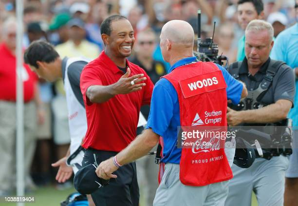 Tiger Woods of the United States celebrates with caddie Joe LaCava after making a par on the 18th green to win the TOUR Championship at East Lake...