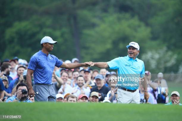 Tiger Woods of the United States celebrates with Fred Couples of the United States on the 12th tee during a practice round prior to The Masters at...