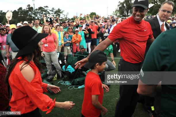 Tiger Woods of the United States celebrates with his girlfriend Erica Herman and son Charlie Axel as he comes off the 18th green in celebration of...
