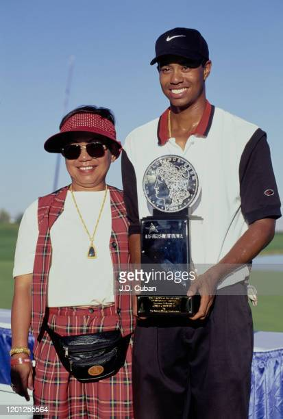 Tiger Woods of the United States celebrates with his mother Kultida Woods and the trophy after winning his first professional golf tournament at the...