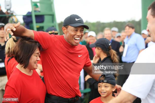 Tiger Woods of the United States celebrates with his son Charlie Axel and manager Mark Steinberg as he comes off the 18th hole in honor of his win...