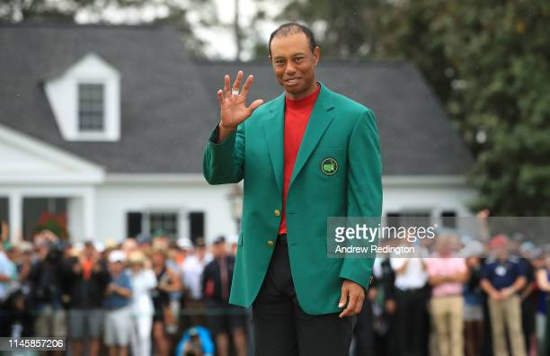 Tiger Woods of the United States celebrates with the Masters Trophy during the Green Jacket Ceremony after winning the Masters at Augusta National...