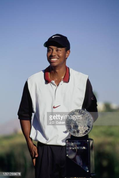 Tiger Woods of the United States celebrates with the trophy after winning his first professional golf tournament at the PGA Las Vegas Invitational on...