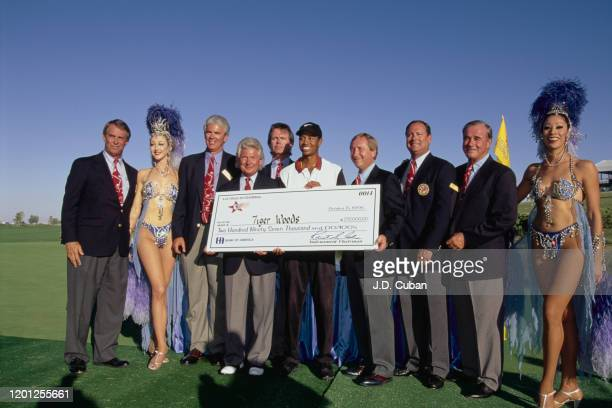 Tiger Woods of the United States celebrates with the trophy and a cheque for $297,000 after winning his first professional golf tournament at the PGA...