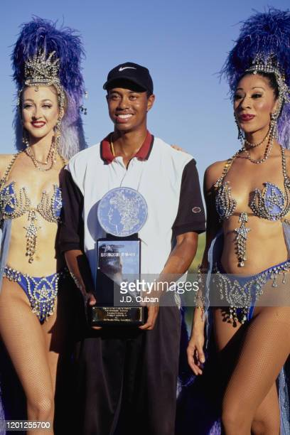 Tiger Woods of the United States celebrates with the trophy and two Showgirl performers after winning his first professional golf tournament at the...