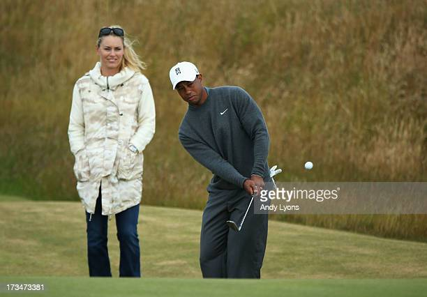 Tiger Woods of the United States chips the ball while skier Lindsey Vonn watches ahead of the 142nd Open Championship at Muirfield on July 15 2013 in...