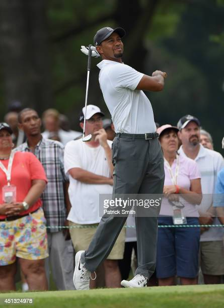Tiger Woods of the United States drops his club after hitting his tee shot on the second hole during the second round of the Quicken Loans National...