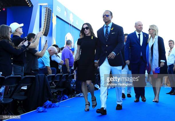 Tiger Woods of the United States girlfriend Erica Herman Captain Thomas Bjorn of Europe and girlfriend Grace Barber depart the opening ceremony for...