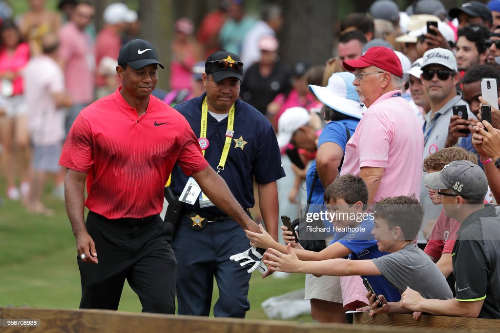 Tiger Woods of the United States gives his glove to young fans during the final round of THE PLAYERS Championship on the Stadium Course at TPC Sawgrass on May 13, 2018 in Ponte Vedra Beach, Florida.